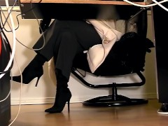 Under desk view of a horny secretary masturbating in pantyhose and boots