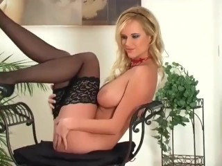 Big boobed blonde in panties and stockings showing her shaved pussy