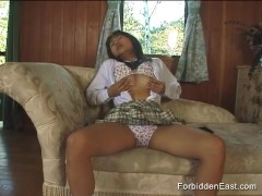 Young Asian girl in socks and pleated skirt teases her pussy with toys