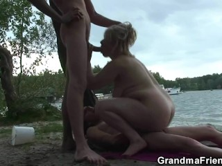 Blonde old women swallows two cocks outdoor