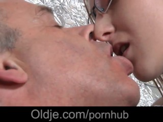 Freckled redhead with glasses making blowjob to older guy