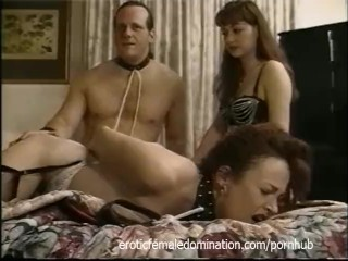 Raunchy bitch sucks on a strap-on while a dude watches