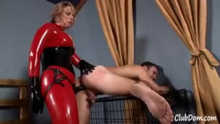 Goddess Brianna in red latex fucks her male slave until he shakes  kink latex fake tits strapon humiliation femdom catsuit blonde shaking