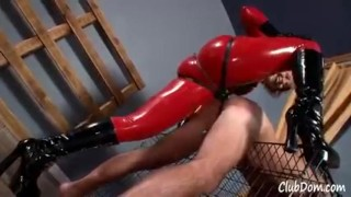 Goddess Brianna in red latex fucks her male slave until he shakes femdom catsuit kink blonde fake tits strapon humiliation latex shaking