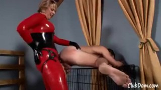 Goddess Brianna in red latex fucks her male slave until he shakes  kink latex shaking fake tits strapon humiliation femdom catsuit blonde