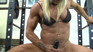 Muscle babe fucking a dildo in the gym