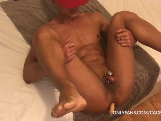 Caged Jock playing with anal beads