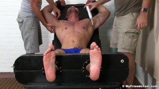 Julian Knowles is restrained and tickled by two kinky studs
