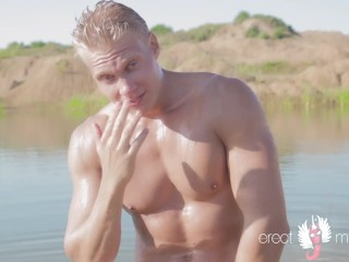 Blonde muscle guy masturbating his wet cock in the lake water