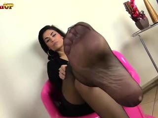 Brunette nude in pantyhose smells her feet